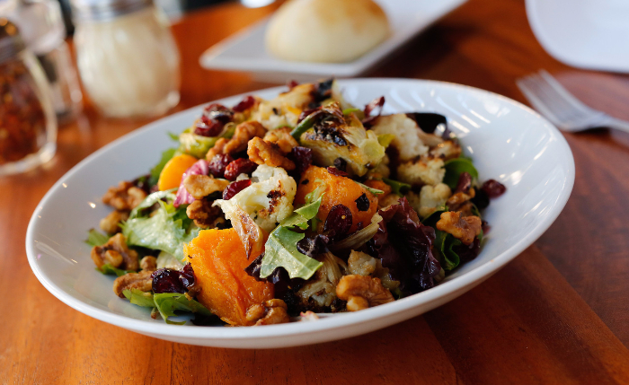 Roasted Vegetable Salad set at a table with condiments