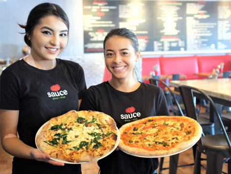 Sauce Team Members displaying pizzas
